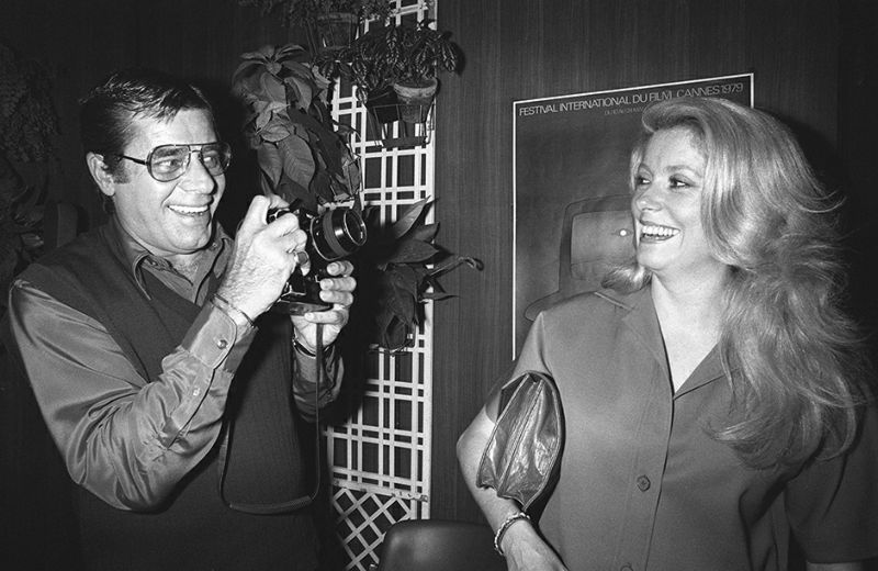 US actor Jerry Lewis holds his Nikon camera before taking a picture of French actress Catherine Deneuve during the 32nd International Movie Festival in Cannes, 24 May 1979. / AFP PHOTO / RALPH GATTI