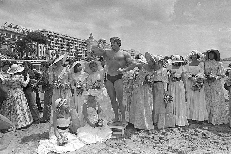 "FILE - In this May 20, 1977 file photo, Arnold Schwarzenegger shows off his body for an appreciative beach audience in Cannes, France, ahead of the presentation of his film ""Pumping Iron"" at the Cannes Film Festival. The Cannes Film Festival officially gets underway on Wednesday, May 11, 2016 and as usual it's set to be one of the most dazzling events in the European entertainment calendar. The festival, in its 69th year, brings a mix of Hollywood A-listers and world cinema auteurs to the French Riviera. (AP Photo, File)"